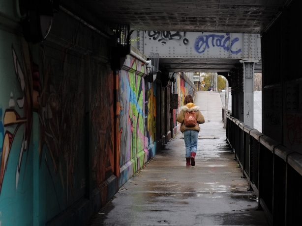 a woman walks along a wet sidewalk under a train bridge, railling on one side, street art on the wall on the other side.