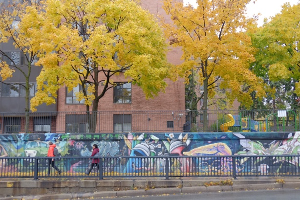 people walking on a sidewalk that passes by a long mural painted by wallnoize, many small murals joined together, apartment buildings with large trees with yellow autumn leaves in the background, Bloor West,