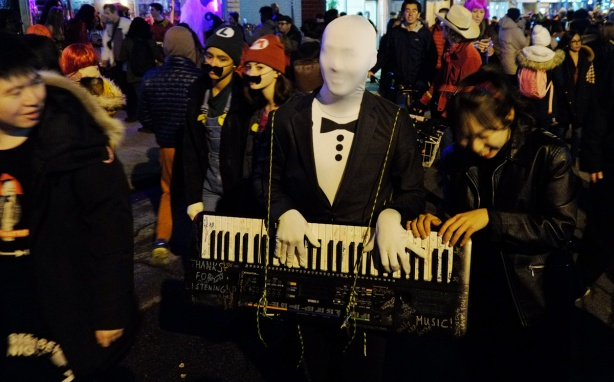 man in black tux with white cloth overhis face plays a keyboard that he has around his neck