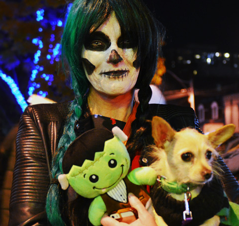 A woman in long braids holds a green fabric doll and a small dog in her arms. Her face is covered with makeup that makes her look like a skull with large black eyes, a black nose and a mouth with notches (stitches?)