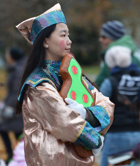 a woman with long black hair stands waiting for her turn in the parade, wearing a shiny blue and gold costume and holding an oversized replica of a gingerbread cookie shaped like a Christmas tree with green frosting and red frosting