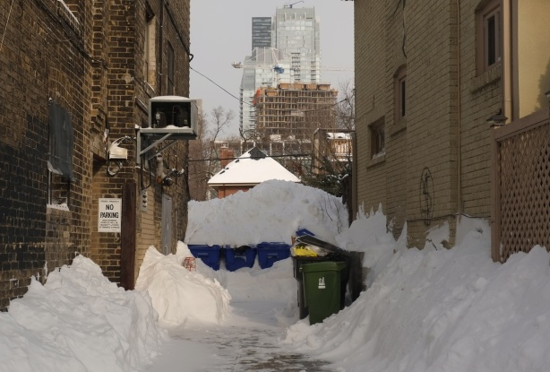 a small alley in winter, garbage bins covered with snow, mounds of snow,