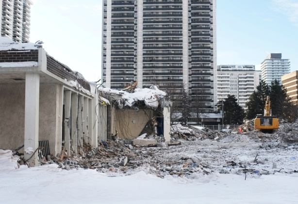 small part of a school remains, debris scattered on the snow, digger at work in the background, apartment building in the distance