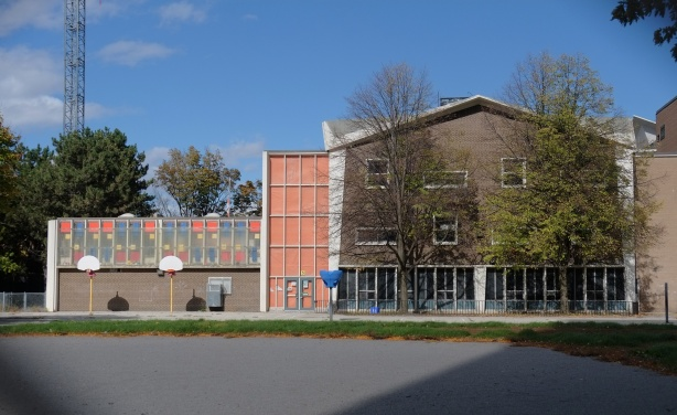 west end of Daviville public school with it's coloured panels on the upper floor, basketball nets in front, pavement
