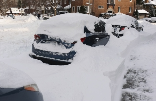 cars parked on the side of a residential street in the city, covered with snow, after a snowstorm, day time, houses across the street.