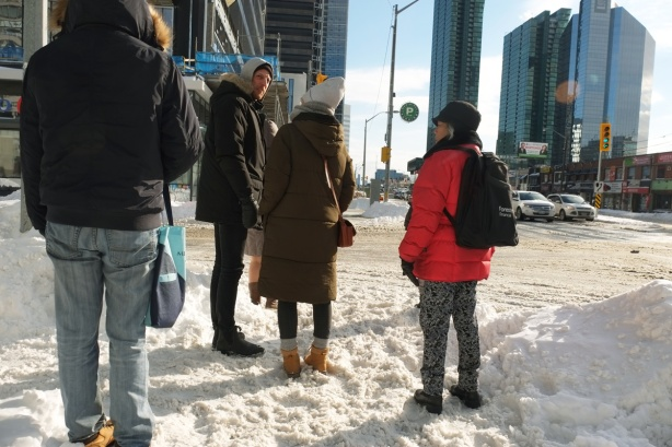 four people standing at an intersection, winter, lots of snow, waiting for the light to turn green, Yonge Street. People wearing winter clothes and boots, hats, parkas.
