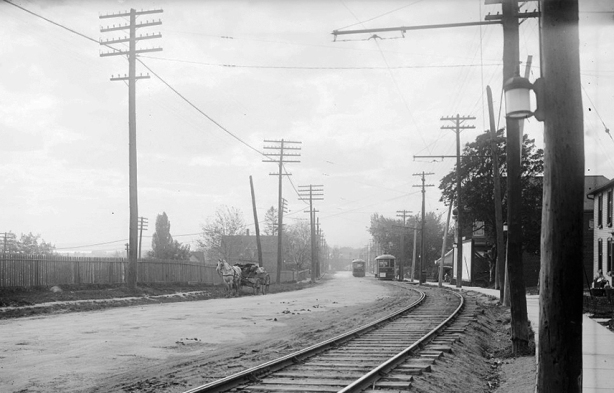 old black and white picture from 1922 of a dirt street with a street car track, hydro poles beside the road and a house