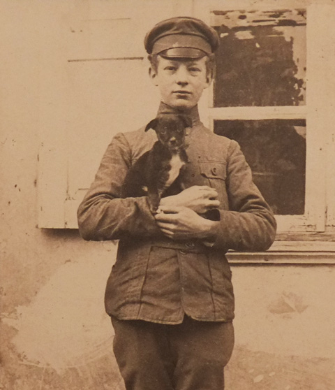 part of an old sepia tone photo of a young man in a soldier's uniform, holding a small dog, World War 1 era, hanging on a wall at the Art Gallery of Ontario