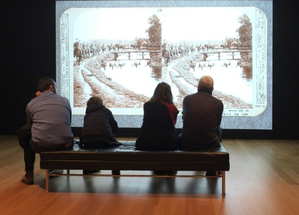 four people sitting on a bench in a gallery looking at a large video screen that is showing images of world war one era stereoscope pictures.