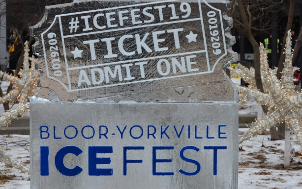 ice sculpture that says, in blue, Bloor Yorkville Icefest, and then above it another sculpture that looks like a ticket, says admit one