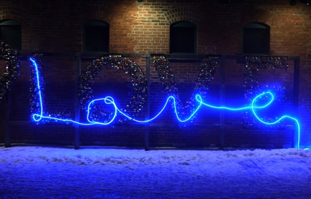 a band of blue light writes the word love in cursive, laid on top of a LOVE sign that is covered with locks.