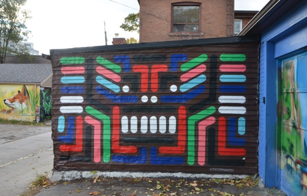 bars, dots, and stripes of colour on a black background, mural in a lane