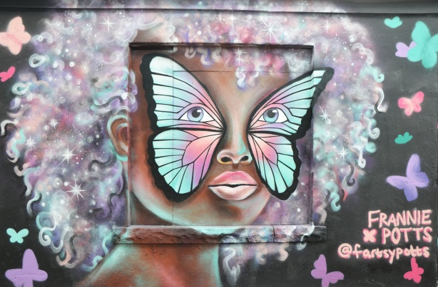 painting by Frannie Potts, a street art face on a garage, woman, with large curly afro style hair in pale colours, with a butterfly painted covering her eyes and cheeks.