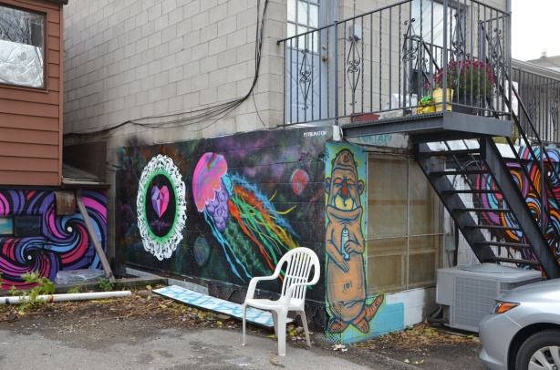 white plastic chair outside in alley in front of a mural of a jellyfish and a heart