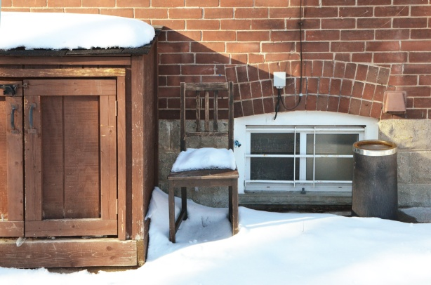 wooden chair outside, against the side of a house, snow on it.