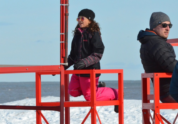 a young woman in pink snow pants is kneeling on a red metal structure, outdoors, snow,