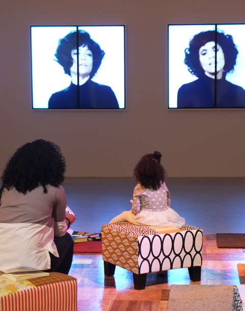 a mother and young daughter sit on seats in a room at the Art Gallery of Ontario, watching videos by Mickalene THomas as part of her Femmes Noires exhibit