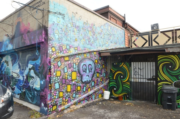 murals in Feel Good Lane, including one by Chris Perez in which a car is parked in front of.