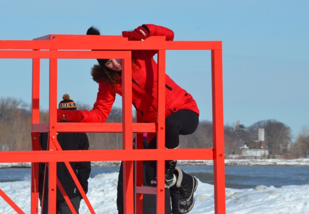 a woman in a red parka is climbing onto an elevated red metal seat