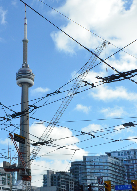 CN tower, blue sky with some clouds, a construction crane and lots of streetcar wires. There are some glass condo buildings in the background. Street sign that says King St., traffic lights