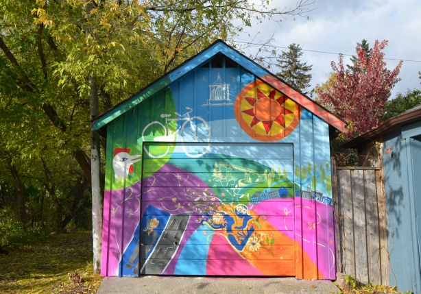 colourful mural covering all of the front of a building that is a garage, abstract sun in top right corner, blue sky, green hill,