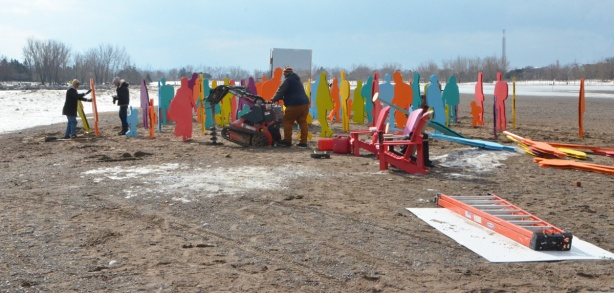 constructing an art installation on the beach in the winter, Woodbine Beach, Winter Stations, colourful life size plywood cutouts of people