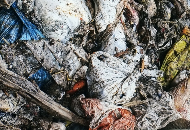 detail of part of a large photo mounted on an exterior wall in Ontario Square, part of a series called Our Desires Fail Us by Sean Martindale and JP King. shows a pile of garbage