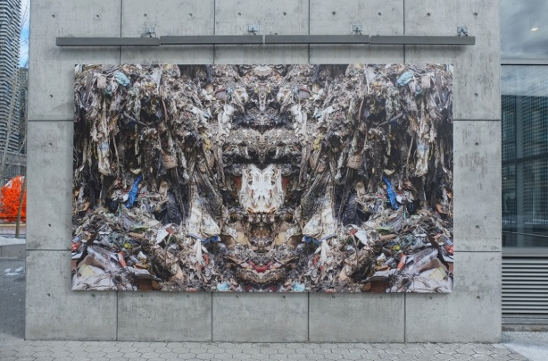 a large photo mounted on an exterior wall in Ontario Square, part of a series called Our Desires Fail Us by Sean Martindale and JP King. shows a pile of garbage