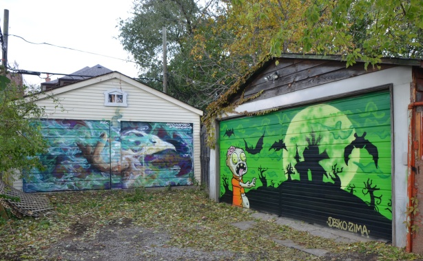 two murals on garage doors in Feel Good Lane, one a green halloween-like scene with silhouettes of bats the other is a marine scene