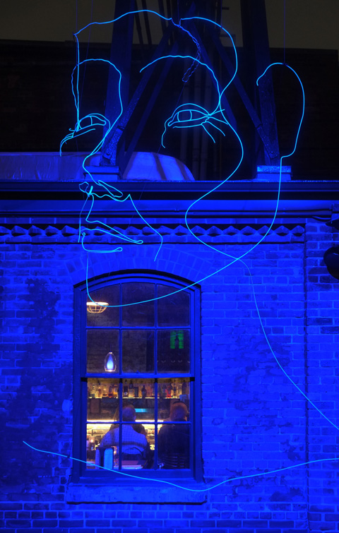blue lights shine against an exterior brick wall of a restaurant, window - looking in the window you can seen people sitting at a table. A large art installation of a woman's face outline in blue light hovers above the window.