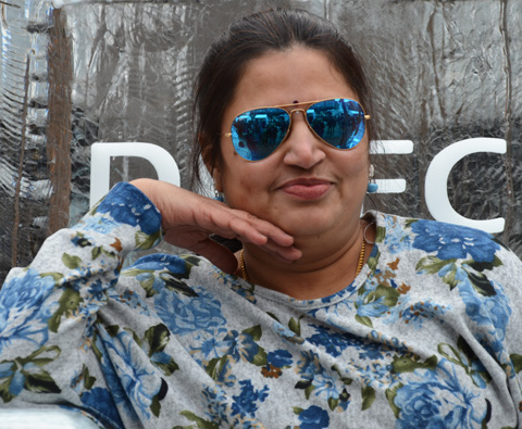a woman in blue sunglasses poses