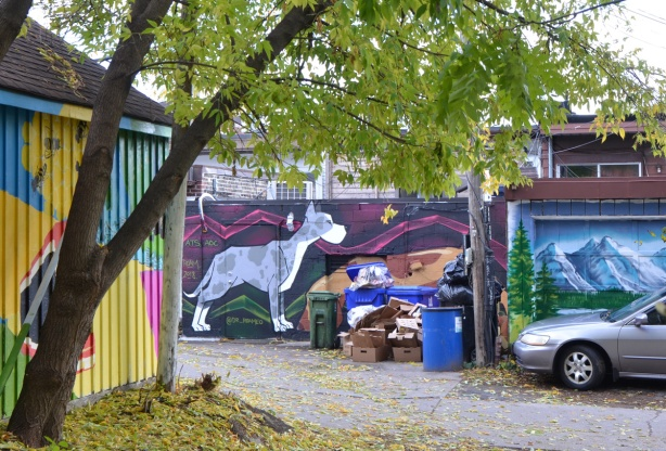alley with murals painted on garages and on the sides of walls, large grey dog painted on a wall, trash cans and recycling bins in the alley too