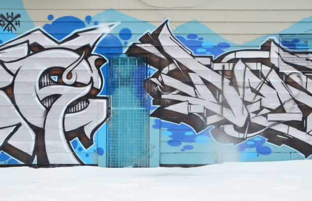 exterior of a building, graffiti covers the wall, black and white tag on blue background. Door in wall is also covered in the blue