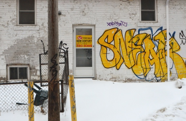 small white building with snow in front, for sale sign in the door, yellow graffiti on the exterior wall to the right of the door, old chair behind the fence to the left of the door