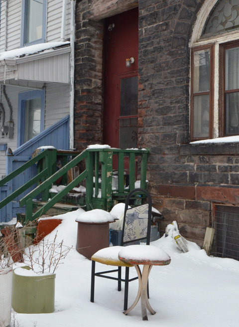 greyish stone house with dark red front entrance, small porch with dark green wood railing, table and chair left on front yard, covered with snow
