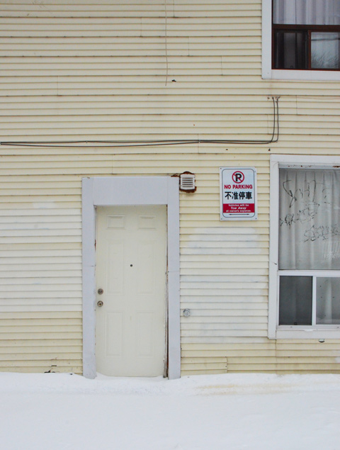 pale cream coloured building with white door frame around cream coloured door, snow in front, no steps in the snow to the door. No parking sign beside the door