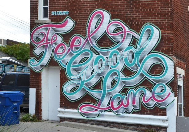 street art on a brick wall in a lane, text, cursive that says Fell Good Lane, painted in blues, white and pink by Spud bomb .
