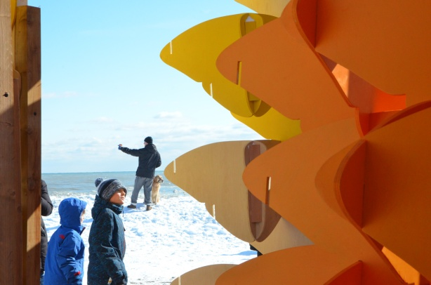 part of 'Forest of Butterflies' sculpture in the foreground, along with two boys who are looking at it In the background, standing on a hill of snow, is a man taking a selfie with his golden lab dog