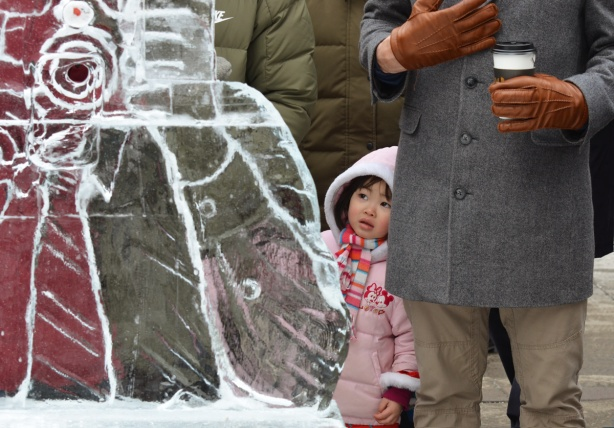 a little girl in pink looks out from behind a man an ice sculpture