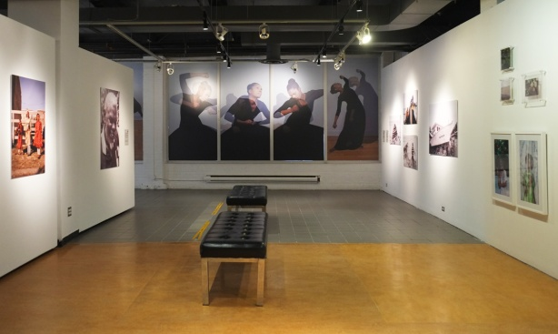 part of art gallery at Harbourfront, wood floors, black bench in the middle, some photos on the two side walls, four large photos on the back wall, a series of four photos by Stella of the same black woman in a number of poses.