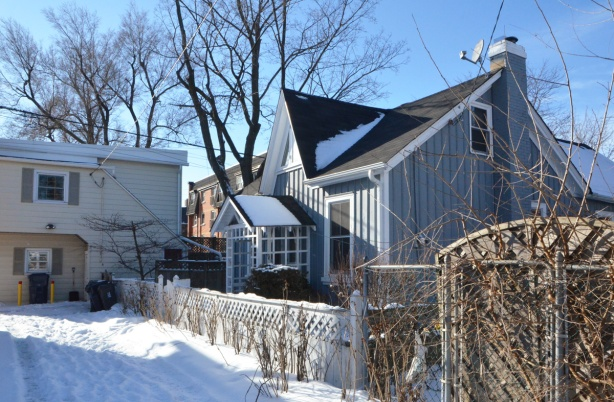 a workers cottage that fronts onto a snow covered lane, grey vertical wood paneling on the outside, black roof
