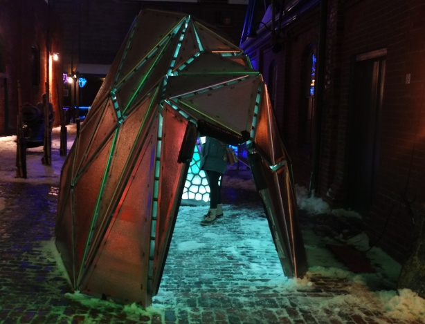 light art installation at Distillery District, like a small tent or hut that you can go inside, tiny triangle of colour, by artist Taylor Dean Harrison, looks like stained glass