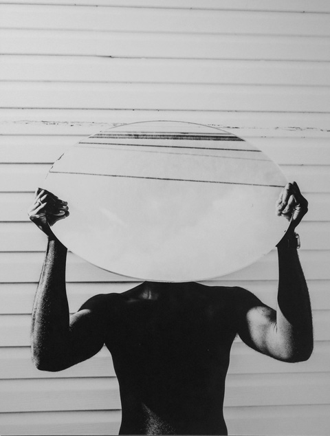 black and white photo by Jah Grey of a black man holding a large round mirror over his head and in front of his face