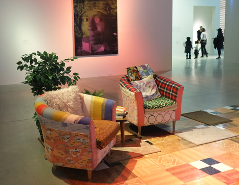 furnishings, comfy armchairs and a carpet on the floor, turing a room at the AGO into a livingroom. On a wall in the background is a piece by Mickalene Thomas as a tribute to the Colour Purple