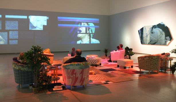 people sitting, furnishings, comfy armchairs and a carpet on the floor, turing a room at the AGO into a livingroom, one wall has video (or videos) playing over its entire surface