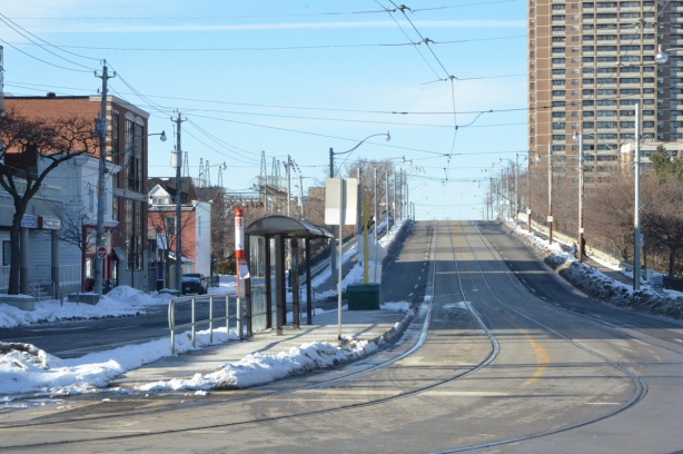 looking north up Main street from Gerard, streetcar tracks with a bus shelter in the middle of the street. old style bus shelter, Main street then goes up, as a bridge over the train tracks. Highrise apartment building in the background.