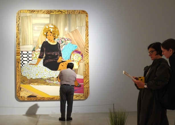 a man is looking at a large painting by Mickalene Thomas of a black woman sitting on a sofa. Two women in the foreground