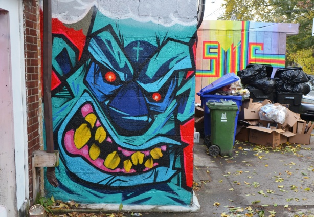 gnarly monster face painted on the side of a small wall, bllue, with big yellow teeth and small red eyes