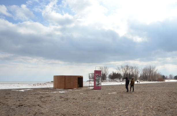 the circular art installation 'Mind Station', wood, on the beach beside Lake Ontario on a winter day, two men walking towards it, trees in the distance