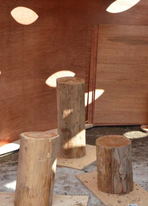 three wood stumps stand upright on the ground, interior of art installation